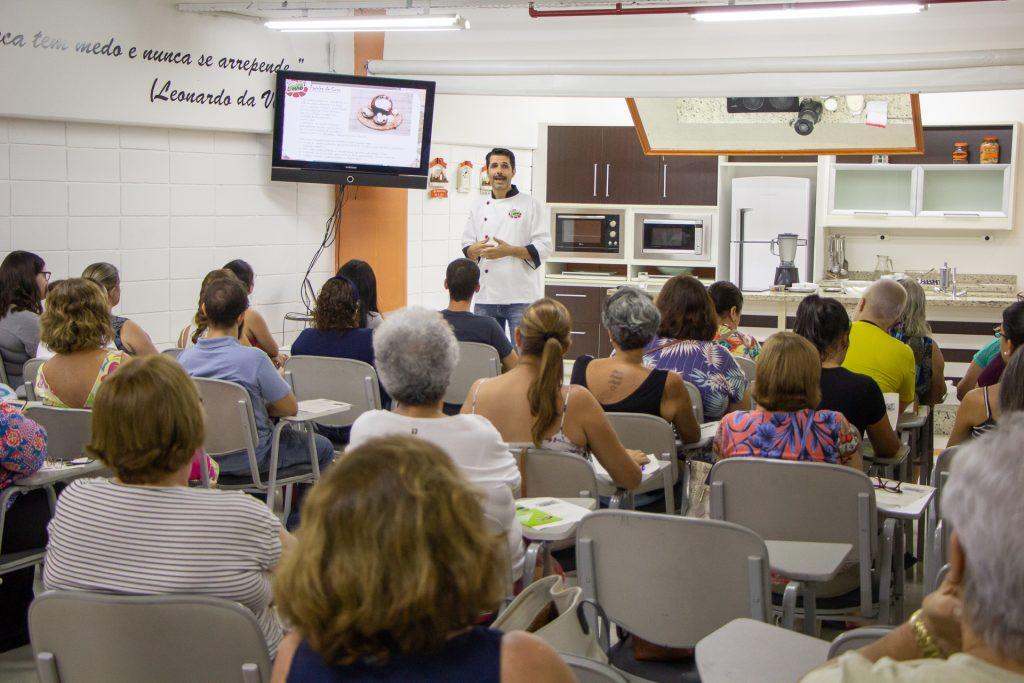 Foto da parte de trás de um grupo de pessoas sentadas em uma sala com uma tv e um chef de cozinha de pé, dando um dos cursos. Ao fundo, uma bancada e uma cozinha.